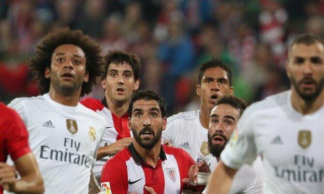Jugadores de Athletic Bilbao y Real Madrid esperan un centro. Conoce las cuotas del Athletic Club Bilbao vs Real Madrid.