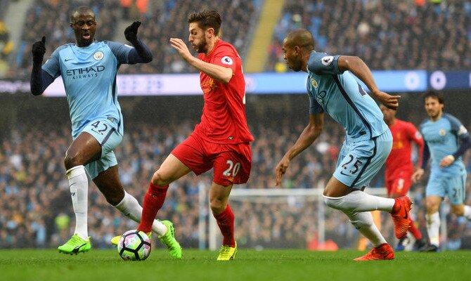 Jugadores Reds y Citizen disputan un balón. Conoce las cuotas del Liverpool FC vs Manchester City.