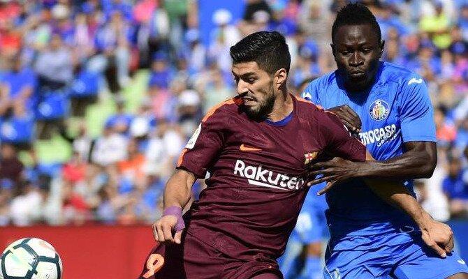 Luis Suárez (izquierda) pugna por un balón con Djené. Conoce los pronósticos del Barcelona Vs Getafe.