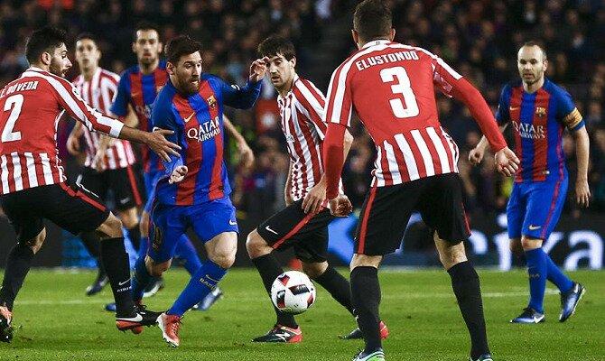 Messi conduce un balón entre jugadores del Athletic. Conoce las cuotas del FC Barcelona vs Athletic Club Bilbao.