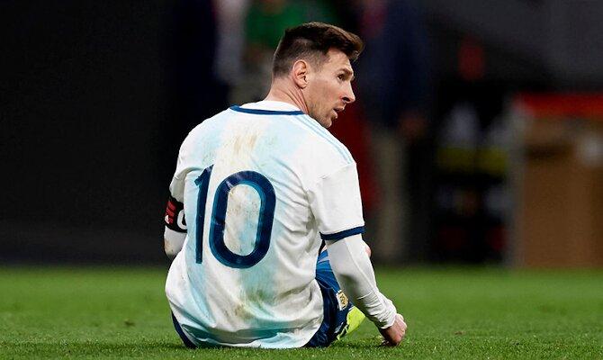 Leo Messi aparece sentado sobre el césped. Cuotas Argentina vs Chile. Apuesta con los mejores picks.