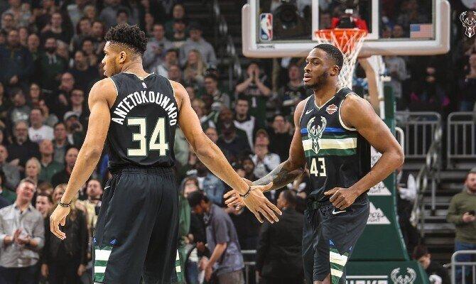 Antetokounmpo choca la mano con un compañero. Cuotas y picks Milwaukee Bucks vs Atlanta Hawks, NBA.
