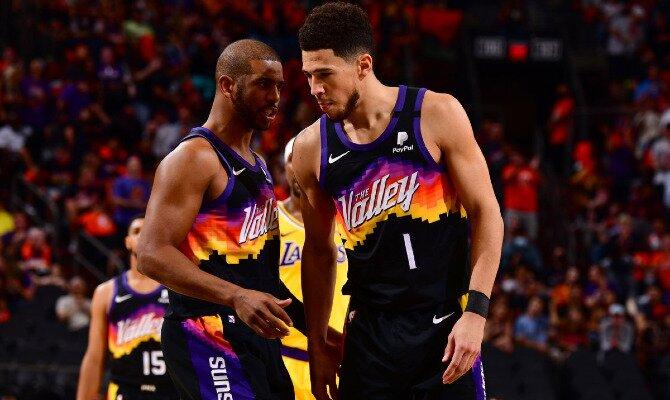 Devin Booker y Chris Paul conversan durante un partido. Cuotas Phoenix Suns vs Milwaukee Bucks, NBA.